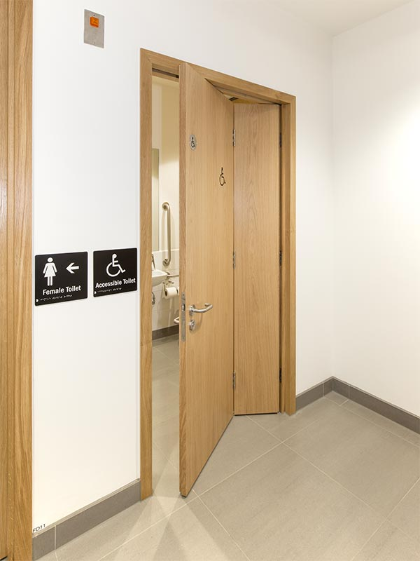 Veneered oak bi-folding accessible wc door supplied by Shadbolt to the Institute of Physics building